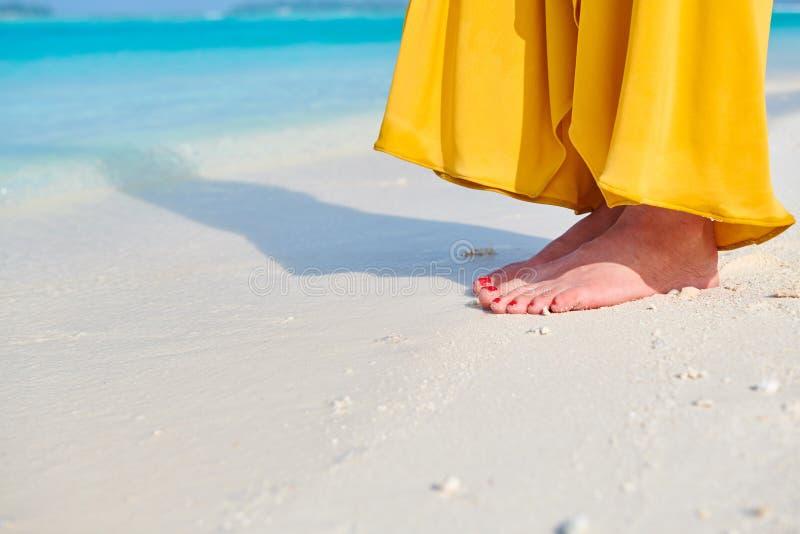 P?s da mulher no vestido amarelo na praia tropical imagens de stock