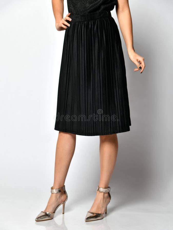 Pés da mulher no vestido preto da saia nas sapatas médias de prata dos montes no cinza imagens de stock royalty free