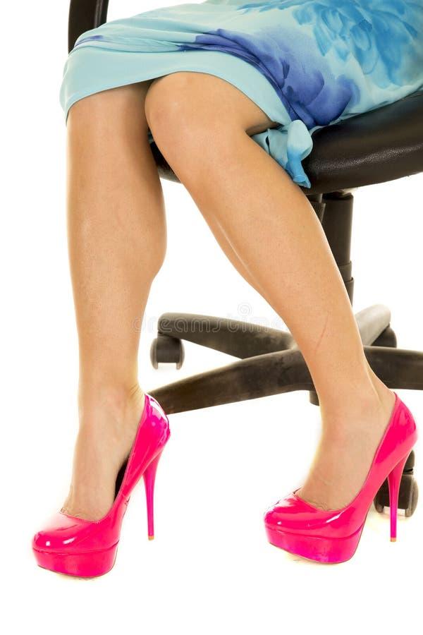 Pés da mulher nos saltos cor-de-rosa e nos pés de assento do vestido azul aguçado a fotografia de stock