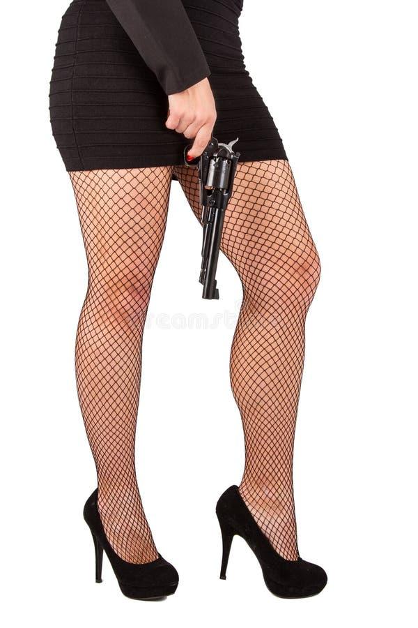 Pés da mulher perigosa com revólver e as sapatas pretas foto de stock
