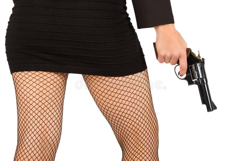 Pés da mulher perigosa com revólver e as sapatas pretas fotografia de stock royalty free
