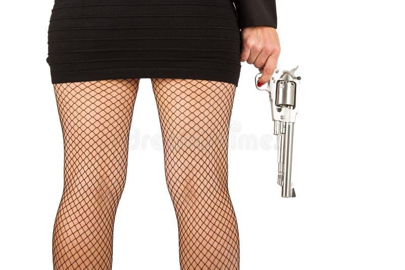 Pés da mulher perigosa com revólver e as sapatas pretas imagens de stock