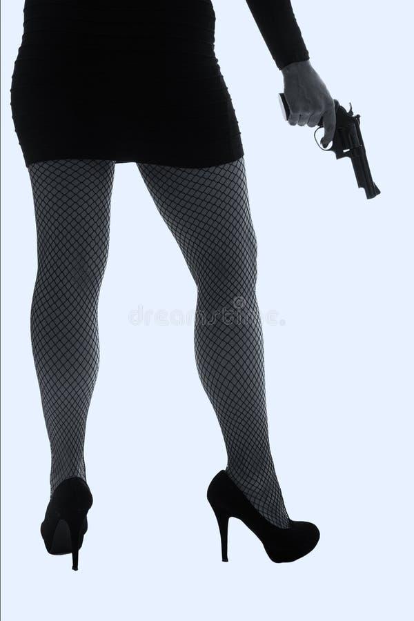 Pés da mulher perigosa com revólver e a silhueta preta das sapatas imagens de stock royalty free