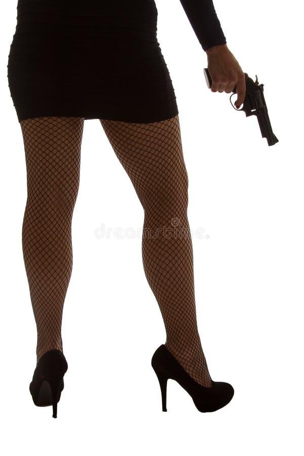 Pés da mulher perigosa com revólver e a silhueta preta das sapatas imagem de stock