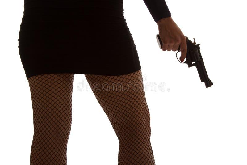Pés da mulher perigosa com revólver e a silhueta preta das sapatas fotos de stock royalty free
