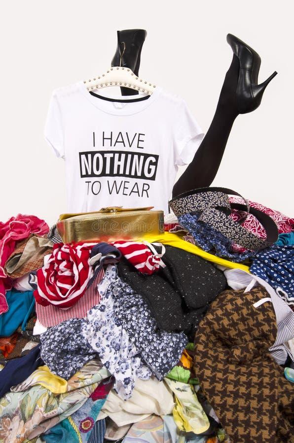 Pés da mulher que alcançam para fora de uma pilha grande da roupa com um t-shirt que não diz nada vestir foto de stock
