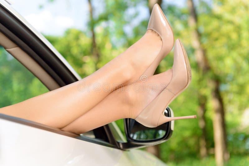 Pés da mulher que olham fora do carro imagem de stock