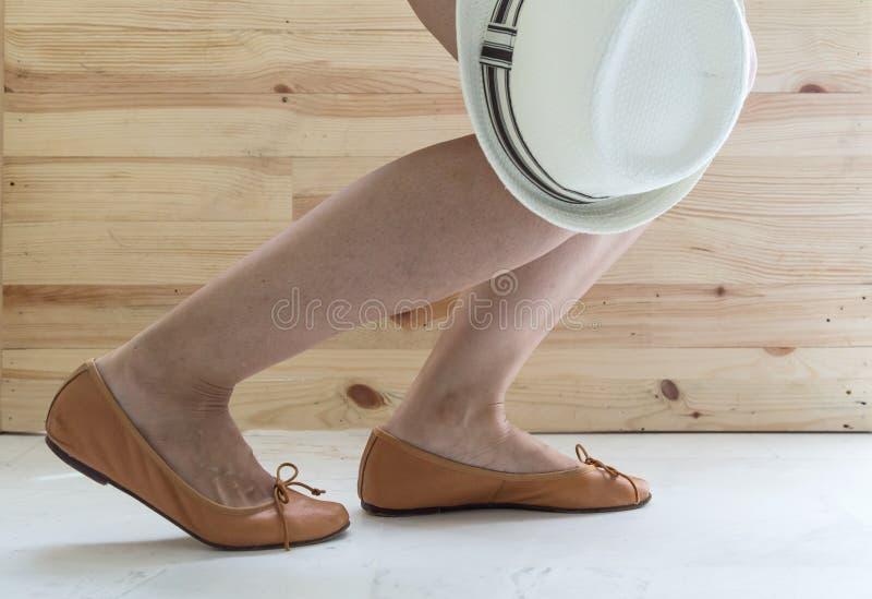 pés da mulher que põr sobre sapatas imagens de stock