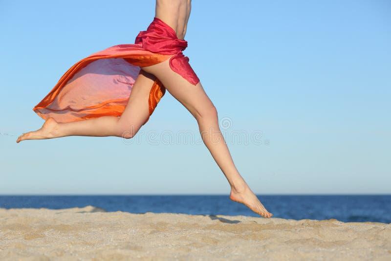Pés da mulher que saltam na praia feliz imagem de stock