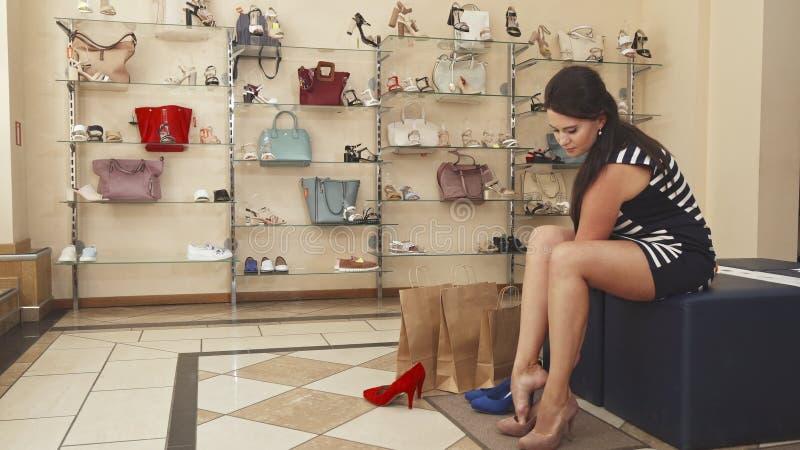 Pés da mulher que tentam sapatas bege sobre imagem de stock royalty free