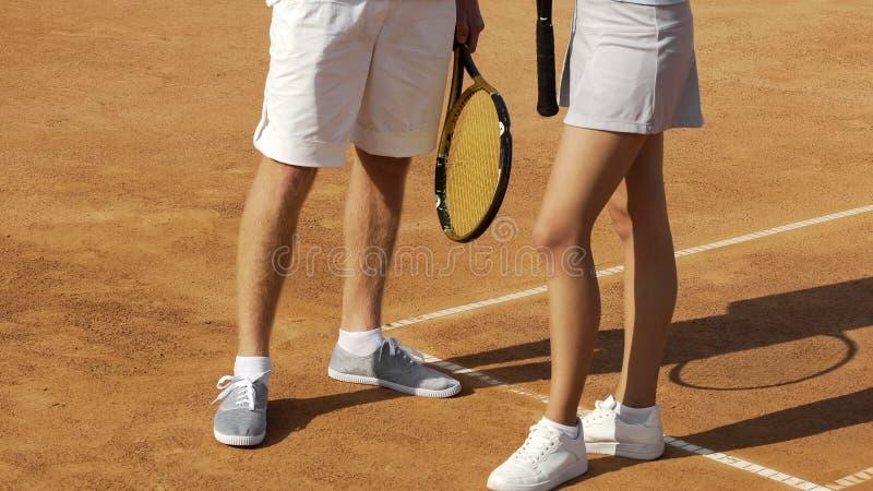 Pés da posição do homem e da mulher no campo de tênis, mantendo o equipamento, fim fotografia de stock royalty free