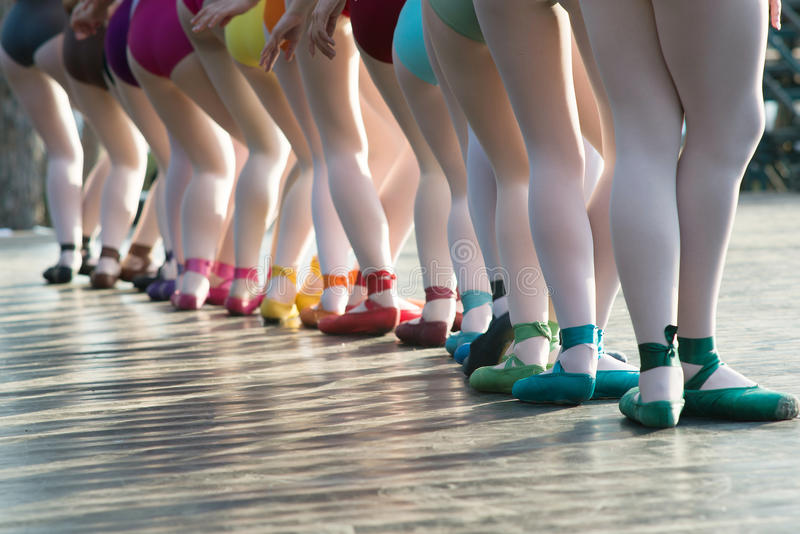 Pés das bailarinas que dançam em sapatas de bailado com diversas cores em s imagem de stock