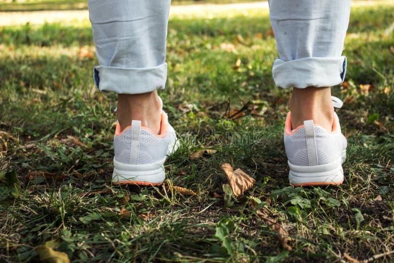 Pés das mulheres no estilo urbano das sapatilhas leves fotografia de stock royalty free