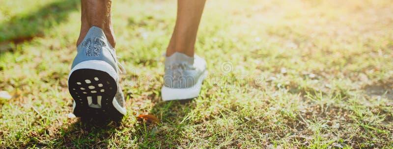 Pés de corrida do homem prontos para a corrida no parque público Estilo de vida e esporte saudáveis Bandeira com espaço da cópia foto de stock royalty free