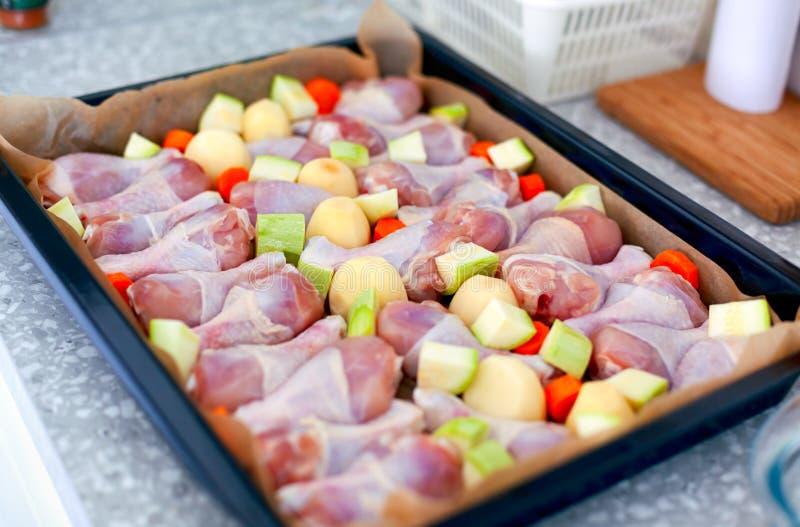 Pés de galinha com os vegetais prontos para cozinhar na bandeja de cozimento na mesa de cozinha imagem de stock
