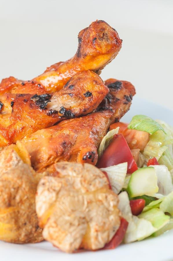 Pés de galinha de Tandoori com as batatas e salada cozidas do bebê na placa branca foto de stock