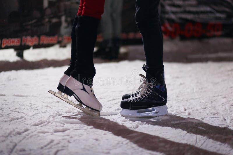 Pés de pares de amor em patins O indivíduo e a menina são contratados na patinagem artística em uma pista da patinagem no gelo na imagem de stock