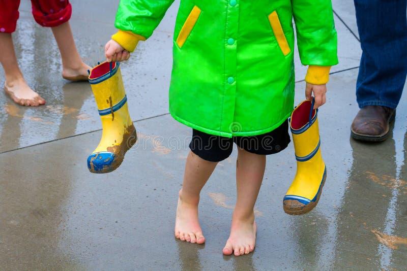 Pés de um menino, de sua irmã, e de seu paizinho após o passeio na chuva imagem de stock