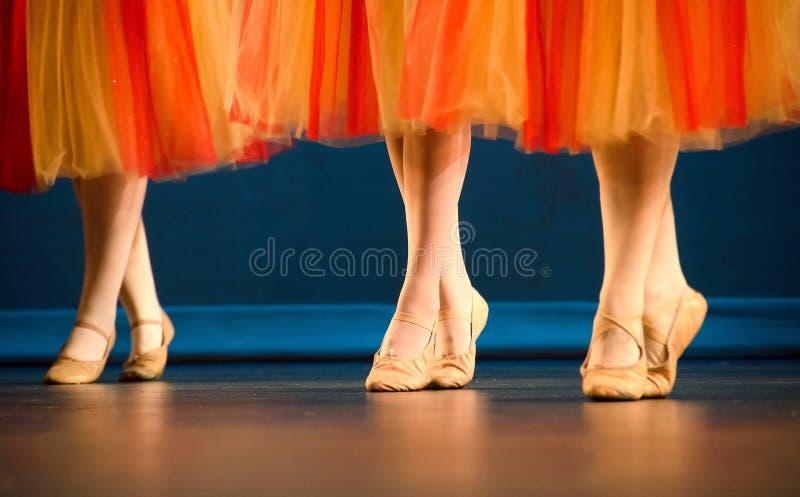 Pés de um trio de dançarinos de bailado em saias do vermelho e do amarelo fotos de stock royalty free