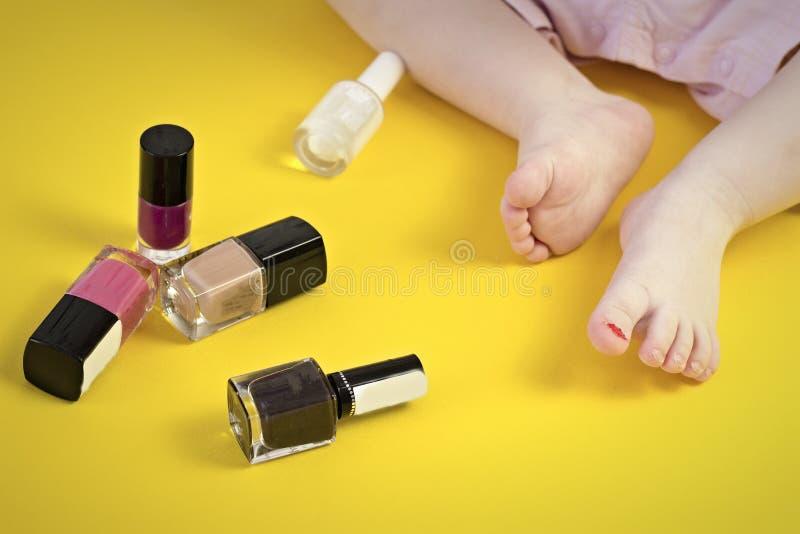 Pés de uma menina e de cosméticos em um fundo amarelo imagens de stock royalty free
