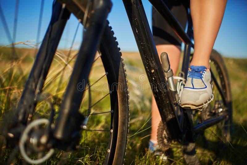 Pés de uma mulher nas sapatilhas com um fim da bicicleta acima imagem de stock royalty free