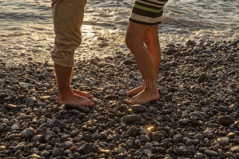 Pés de uma posição nova dos pares no beira-mar, no por do sol agradável fotografia de stock