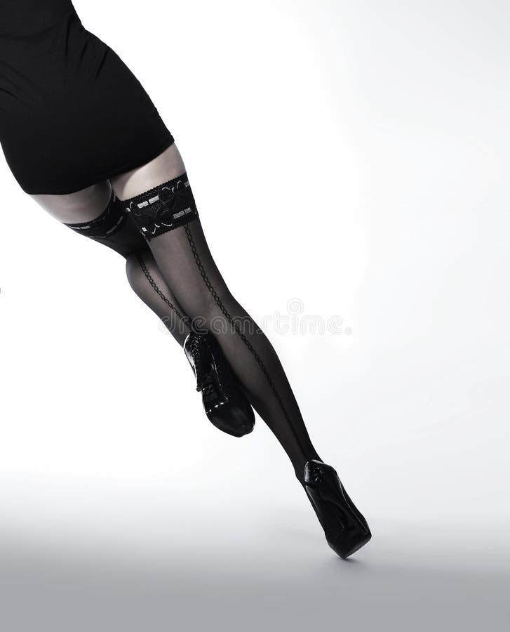 Pés de uns jovens e de uma mulher do ajuste em meias pretas imagens de stock royalty free