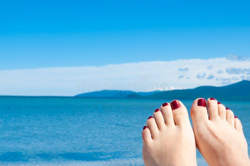 Pés de Womans de encontro ao mar e ao céu azul fotos de stock royalty free