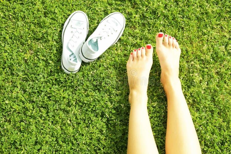 Pés desencapados fêmeas na grama mawed do gramado A jovem mulher que descansa fora com os pés descalços, toma um conceito da rupt foto de stock royalty free