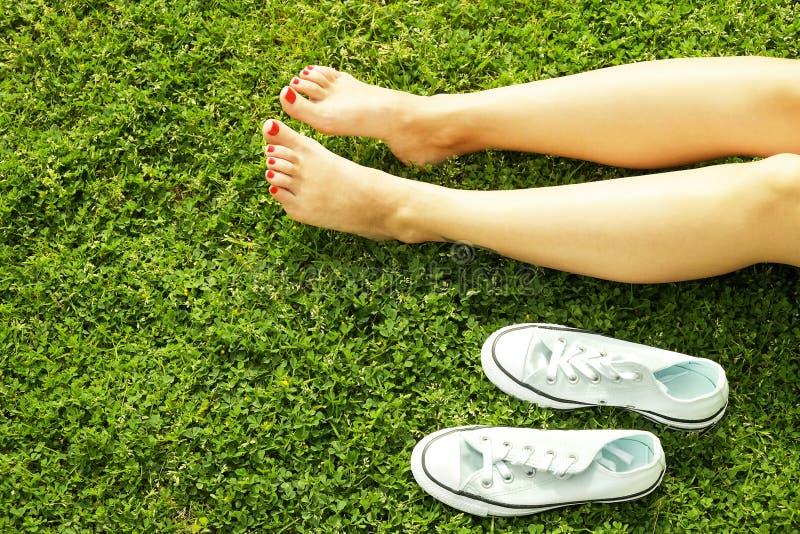 Pés desencapados fêmeas na grama mawed do gramado A jovem mulher que descansa fora com os pés descalços, toma um conceito da rupt fotos de stock royalty free