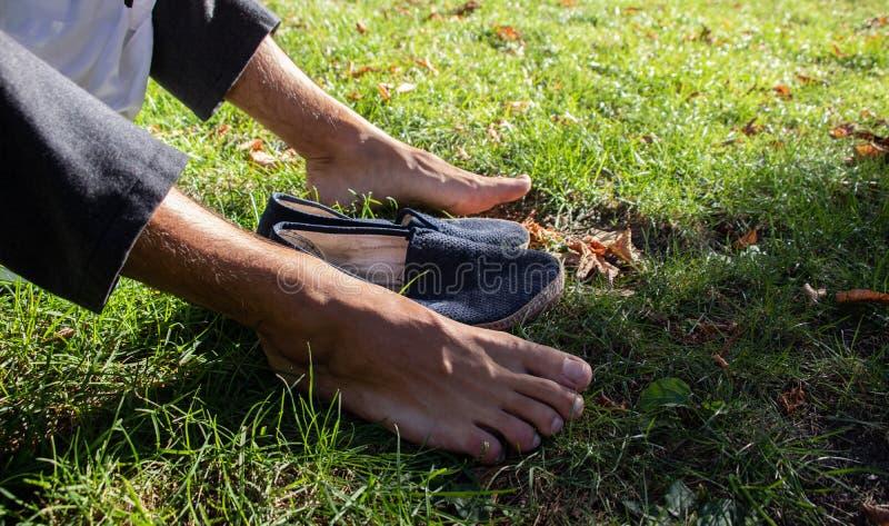 Pés desencapados na grama com sapatas azuis fotos de stock