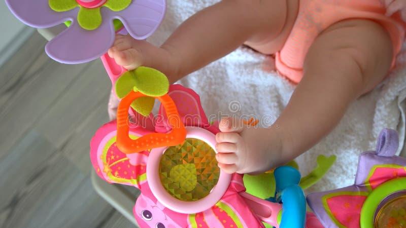 Pés do bebê e brinquedos do chocalho imagens de stock