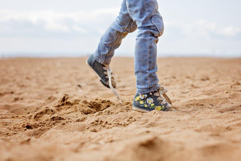 Pés do bebê nas calças de brim e nas sapatilhas que correm na areia no verão fotos de stock royalty free
