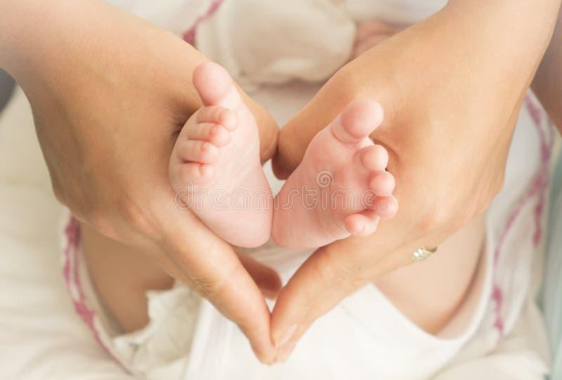 Pés do bebê nas mãos da mãe - forma da lareira fotografia de stock