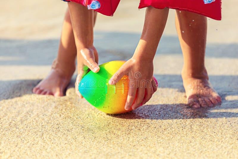 Pés do bebê que andam na bola de rugby de agarramento da praia da areia, criança brincalhão que veste a bola inflável da terra ar imagens de stock royalty free