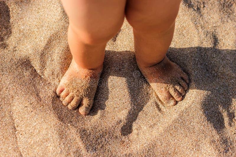 Pés do bebê que andam na praia da areia no verão imagens de stock
