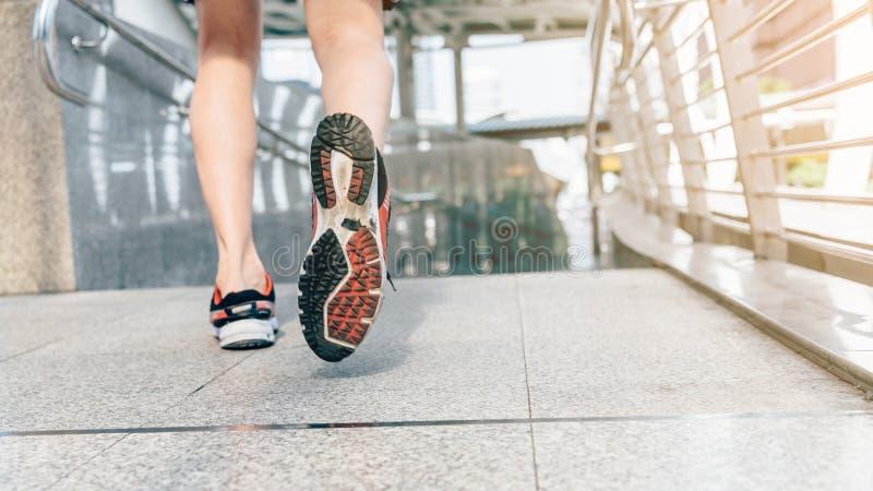 Pés do corredor do atleta que correm no close up da cidade na sapata foto de stock