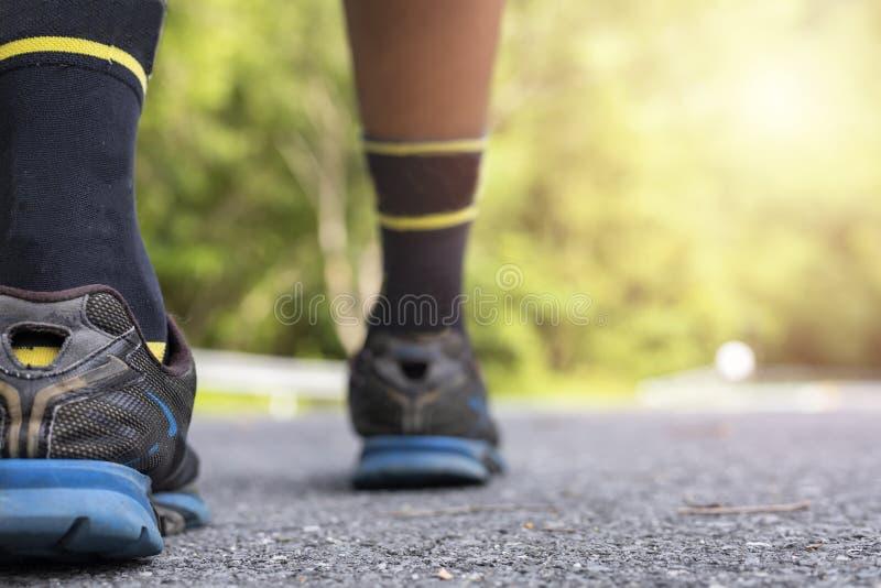 Pés do corredor do homem na estrada no foco macio do bem-estar do exercício do parque e fim do foco acima na sapata imagem de stock