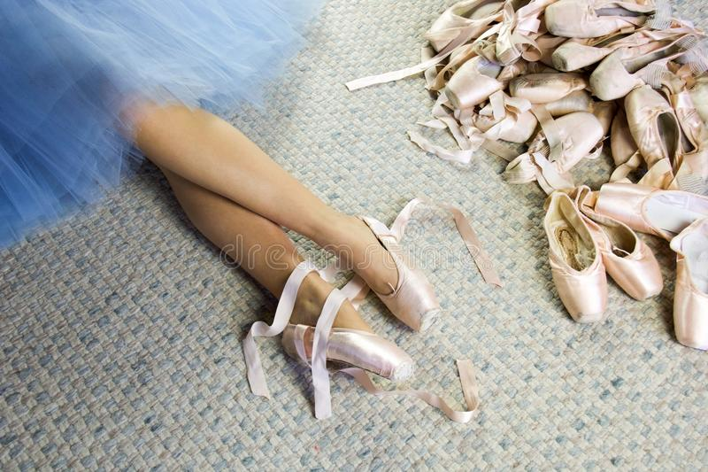 Pés do dançarino de bailado fêmea que encontra-se com sapatas do pointe imagens de stock royalty free