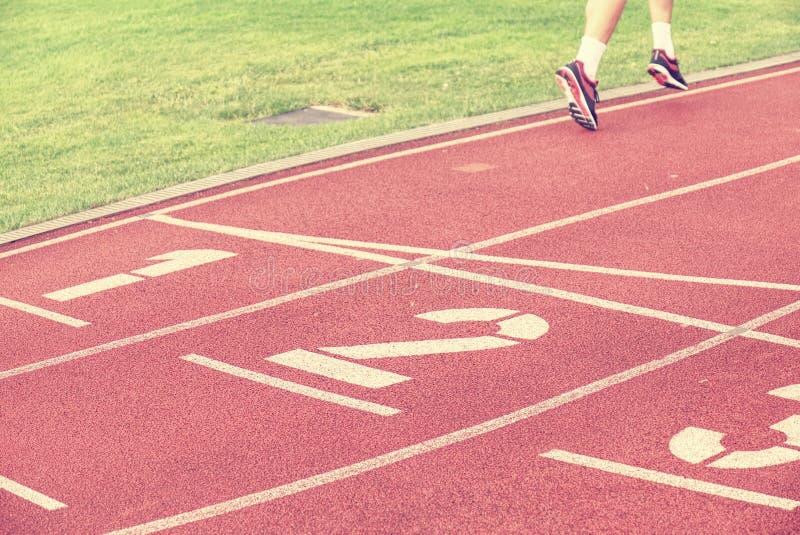 Pés do desportista nos tênis de corrida na trilha do vermelho do estádio fotografia de stock royalty free