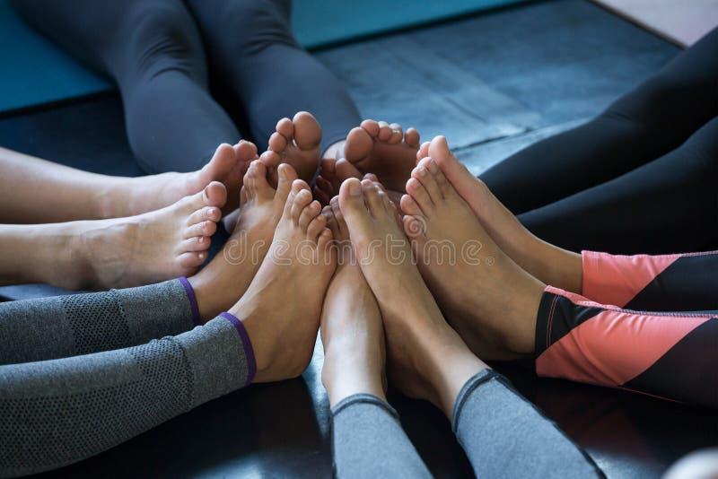 pés do grupo da ioga dos povos da aptidão no gym junte-se ao pé junto fotografia de stock