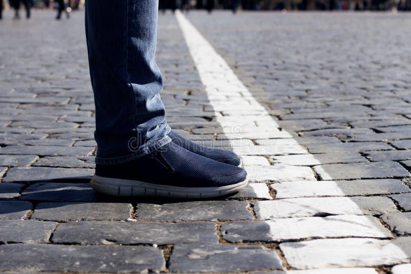 Pés do homem e pés na frente da linha branca Conceito da vida nova ou do projeto novo foto de stock royalty free