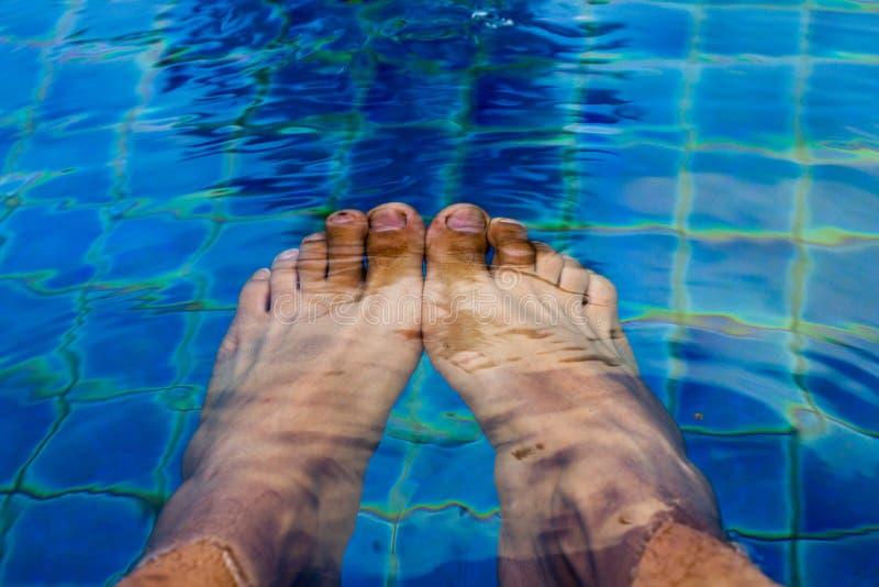Pés do homem na piscina sob a água imagem de stock
