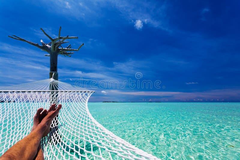 Pés do homem no hammock sobre a lagoa tropical imagens de stock royalty free