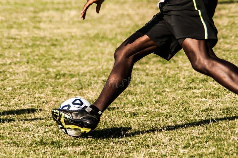 Pés do jogador de futebol na ação imagens de stock