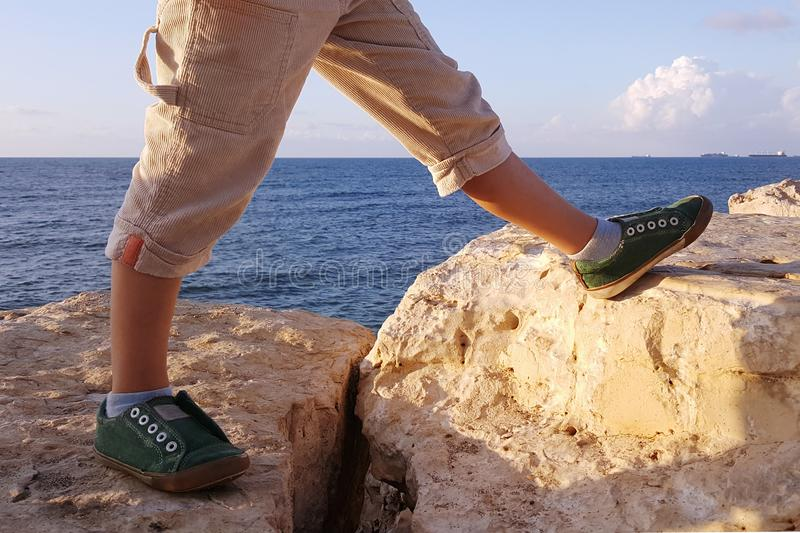 Pés do menino gigante, etapa em pedras, mar fotografia de stock
