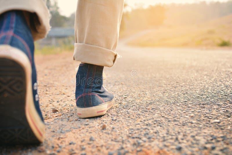 Pés do moderno um homem e uma sapatilha das calças de brim na natureza fotos de stock