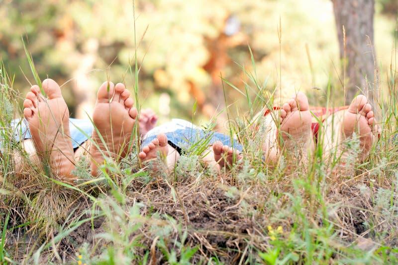 Pés do pai, da mãe e da criança na grama. fotos de stock royalty free