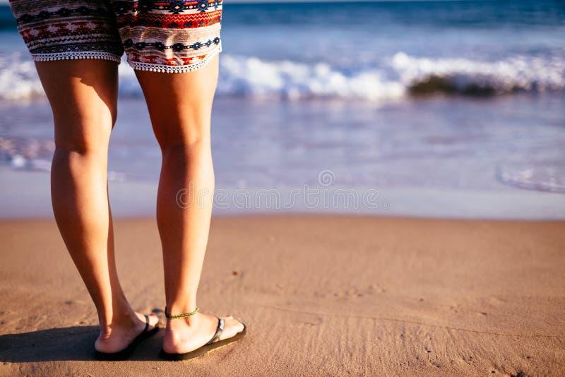 Pés do ` s da mulher na praia fotografia de stock