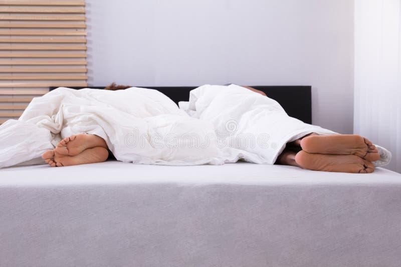 Pés do ` s dos pares que dormem na cama imagens de stock royalty free